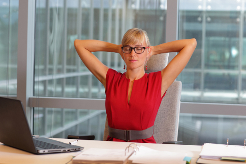 Woman with glasses doing yoga at desk