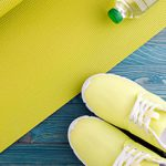 Yellow yoga mat and tennis shoes